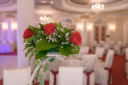 Red roses centerpiece at a wedding reception. Decorative display of a floral arrangement in a large venue.
