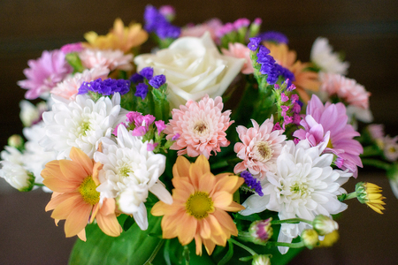 Mixed and colorful autumn flowers bridal bouquet positioned against a dark background 스톡 콘텐츠
