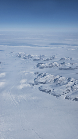 Aerial view of remote deserted frozen surface with mountains and glaciers in southern coast of Greenland