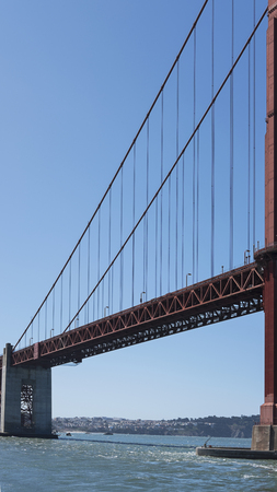 Vertical section of the suspension and cropped view of south tower of the iconic Golden Gate Bridge, San Francisco, California, USA