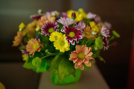 Varied colors blossoms in a rustic bridal arrangement positioned against a dark background. Wedding arrangements, floral setting and ideas for bride morning preparation.