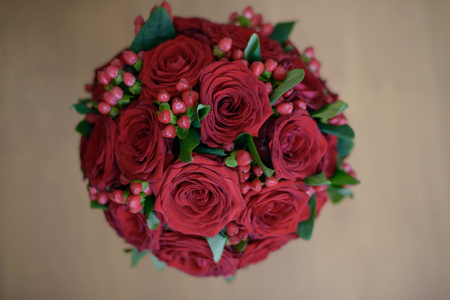 Scarlet roses and berries floral arrangement set on a table, view from above