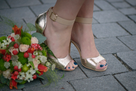 Nahaufnahme junger weißer kaukasischer weiblicher Füße in eleganten goldenen Sandalen mit blauem Nagellack, die von einem bunten Hochzeitsstrauß positioniert sind