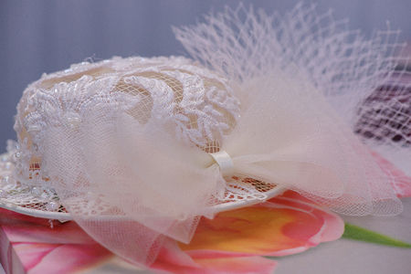 Wedding accessories: white lacy hat resting on a flowery cloth. Bridal ideas, wedding arrangements, ceremony themes suggestions.