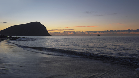 Sunrise over Montana Roja, an unusual, stratovolcanic cone and La Tejita beach, one of the longest, natural beaches in Tenerife, Canary Islands, Spain. Panoramic perspective with natural light