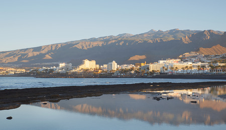 Early morning light with reflection in a natural ocean pool, over the south-west coast of the island, towards the most popular resorts in Costa Adeje,  Las Americas, Tenerife, Canary Islands, Spain 免版税图像