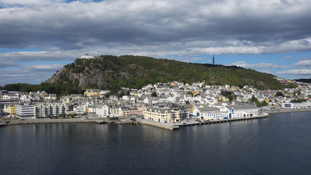 Horizontal shot with perspective from the fjord of Alesund, a tranquil port town with architecture in Art Nouveau style, and Mount Aksla in the background at the entrance to the Geirangerfjord, Norway Stok Fotoğraf - 117691309