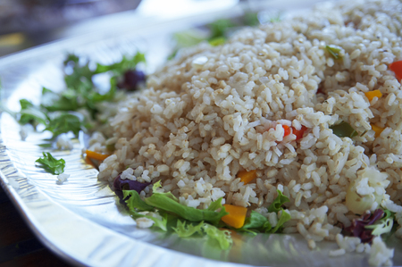 Healthy steamed brown, integral rice with vegetables on a large plate, served on its own or as a side dish, a delicious option for vegetarians or vegans, at a buffet bar, or self-service restaurant Banco de Imagens