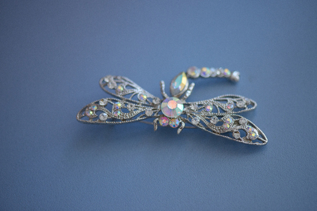 Isolated silver, white gold, platinum dragonfly brooch on a blue suede leather cloth