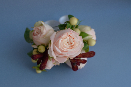 Pink roses and berries small bouquet for table arrangements or boutonniere accessory against solid blue background