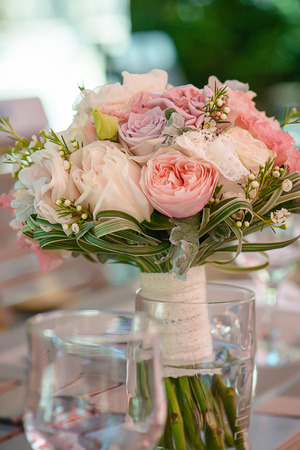 Round bridal bouquet featuring pastel color peonies and roses, lace and greenery, set on a table, with selective focus