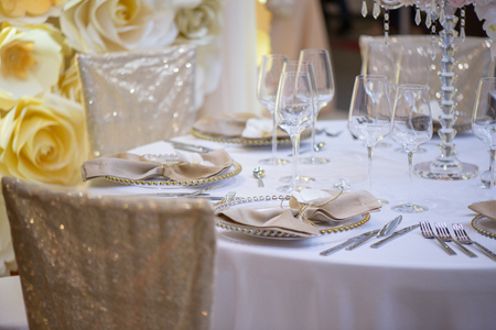 Sitting arrangement at a formal event or fine dining restaurant featuring transparent plates with golden details, glassware and silverware in the order of use set against a paper flowers wall Stock Photo - 119592858