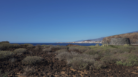Arid volcanic landscape of Malpais de la Rasca, a natural reserve close to Palm-Mar town, with views towards Atlantic Ocean and the tourist resort Los Cristianos, in Tenerife, Canary Islands, Spain 写真素材 - 122865727