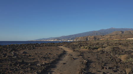 Path through the landscape of Malpais de la Rasca, a natural reserve close to Palm-Mar town, with views towards Atlantic Ocean and the tourist resort Los Cristianos, Tenerife, Canary Islands, Spain 写真素材 - 122865730