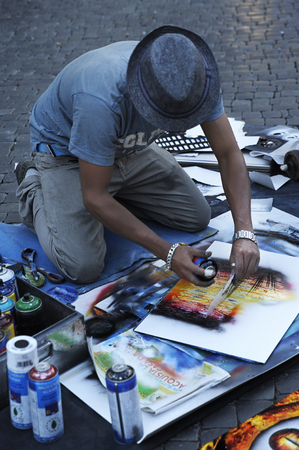 Piazza Navona, Rome - July 4, 2015: Street male artist creates images of the Roman architecture by using and mixing  aerosol paint in Piazza Navona, a popular square among artists, vendors and performers