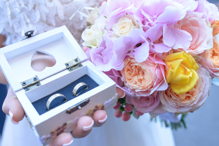 Close-up of brides hands holding a summer wedding bouquet with pink hues and a small white wooden box with wedding bands for him and her Stock Photo