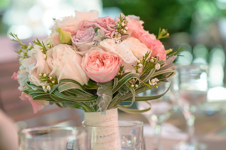 Horizontal shot of elegant peonies, roses and silk bridal bouquet resting on a table at the reception venue, in a transparent vase