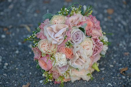 View from above of an exquisite bridal round bouquet featuring roses in different hues of pink, berries and silky peonies positioned on a barren, dark ground