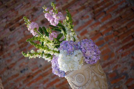 Minimalist white clay decorated flower pot with a spring bouquet featuring pastel hydrangeas, decorative element for a formal event or a wedding, with a terracotta color brick wall in the background Imagens - 124945453