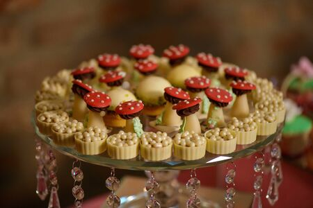 Delicious dessert variety of playful or themed bite-sized cakes and white chocolate cups, displayed on an embellished crystal cake stand, at a wedding reception, a birthday party or a formal event