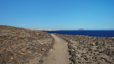 Hiking trail nearby Atlantic through the arid volcanic landscape of the island, views from Montana Amarilla towards Marina San Miguel, outdoor natural attraction in Tenerife, Canary Islands, Spain