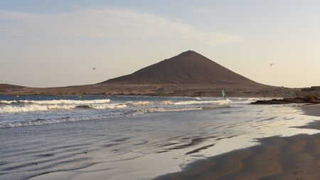 Sunset at El Medano beach towards Montana Roja, a popular beach in the municipality of Granadilla de Abona for services and amenities, for the ideal swimming conditions, for windsurfing or kitesurfing 版權商用圖片