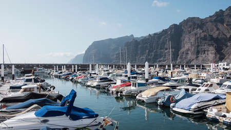 Los Gigantes, Santiago del Teide, Tenerife, Canary Islands, Spain: May 18, 2019 - the yacht marina as seen from the town pier, with the iconic giant cliffs behind known as Acantilados de Los Gigantes 新聞圖片