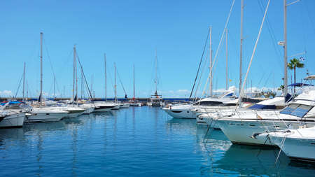 Puerto Colon, Costa Adeje, Tenerife, Canary Islands, Spain - April 5, 2019: yachts, sailboats and catamarans moored alongside the busiest marina with a capacity for 364 anchored boats and 237 moorings 新聞圖片