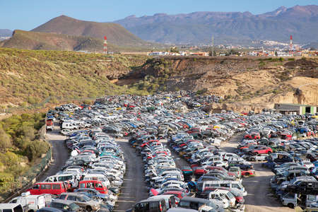 Tenerife, Canary Islands, Spain - April 28, 2019: Stacked up recycled cars, old crashed vehicles used for parts or as metal scrap at a junkyard or a recycling facility in the south of the island