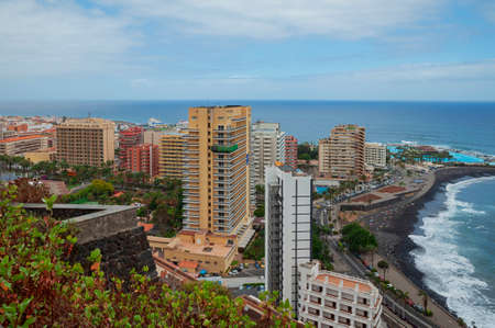 Puerto de la Cruz, Tenerife, Canary Islands, Spain - September 27, 2016: aerial view of the tourist resort and town with tower hotels, the volcanic black sand beach and Lago Martianez leisure park 新聞圖片