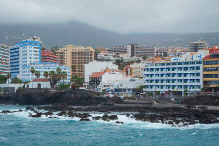 Puerto de la Cruz, Tenerife, Canary Islands, Spain - September 27, 2016: inland views of the tourist resort and town with tower hotels, shops, promenade and rocky coast in a cold, hazy and cloudy day