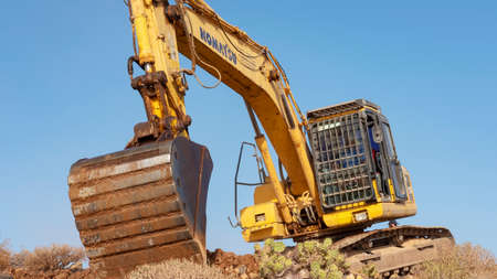 Los Abrigos, Tenerife, Canary Islands, Spain - February 27, 2019: Komatsu mini excavator, heavy machinery with extensive uses performing leveling and terracing, landscaping work for a path construction