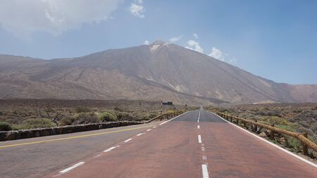 Empty road passing through Teide National Park, with the volcano Pico del Teide in front, situated at high altitude and surrounded by the scarce endemic vegetation, in Tenerife, Canary Islands, Spain