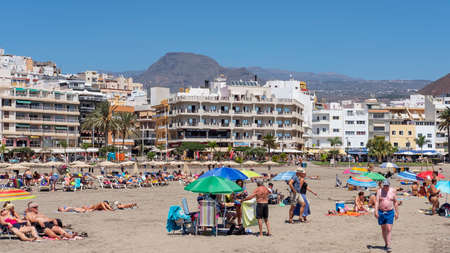 Los Cristianos, Tenerife, Canary Islands, Spain - September 15, 2019: lots of tourists enjoying their vacation in Los Cristianos resort and town, on the crowded vast beach, under the scorching hot sun 新聞圖片