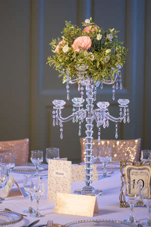 Elegant table arrangement for a formal event, a wedding or a fine dining experience, featuring a gorgeous centerpiece, a crystal candelabra candlestick with a roses and greenery bouquet in the middle