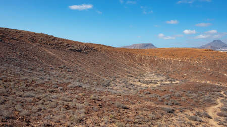 Elevated views of the arid volcanic landscape surrounding the summit of Montana Amarilla towards Pico del Teide and the small terraced villages, in Costa del Silencio, Tenerife, Canary Islands, Spain