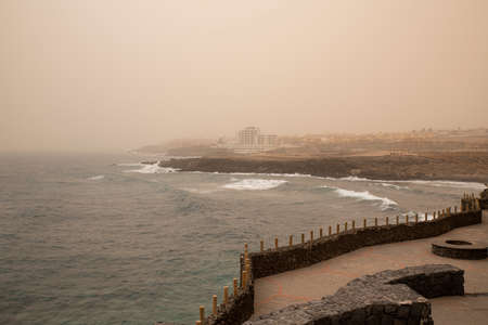Calima weather with low visibility towards San Blas and Golf del Sur, popular southern resorts in Tenerife, as seen from the harbor promenade in the small village of Los Abrigos, Canary Islands, Spain