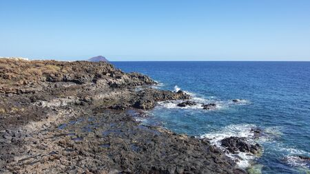 Rough and rocky landscape of the coastal walking path from Montana Amarilla to Amarilla Golf and Golf Del Sur with views of the small fishing villages and Montana Roja, Tenerife, Canary Islands, Spain