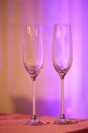 Two empty elegant champagne flutes on a table under artificial purple light, usual recipients for a toast, a welcome or a greeting at a wedding reception, restaurant, formal event or a garden party 版權商用圖片