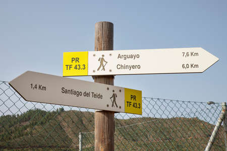 Santiago del Teide, Tenerife, Canary Islands, Spain - February 15, 2020: signposts on the trekking path known as Almendro en flor, marking the distances to Arguayo, Chinyero and Santiago del Teide 新聞圖片