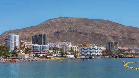 Los Cristianos, Tenerife, Canary Islands, Spain - September 15, 2019: scenic views towards Los Cristianos, popular resort and harbor with many tourists enjoying the calm sea and hot, tropical weather