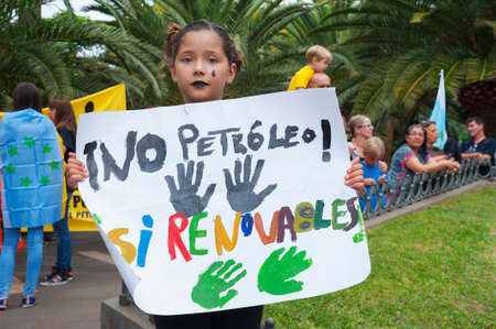 Santa Cruz de Tenerife, Canary Islands, Spain - October 18, 2014: girl holding a placard: No Petroleo, Si renovables meaning No to oil, Yes to renewable, protest against oil drilling in the Canaries