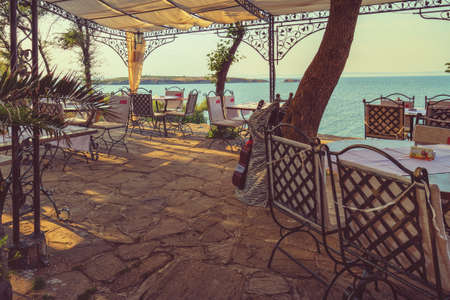 sulight: Toned picture of the outdoor restaurant with seaview. Stock Photo