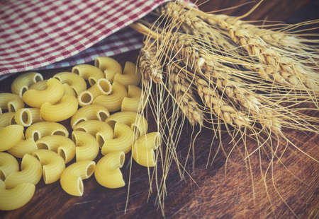 foodstuff: Vintage toned picture of the ears of wheat with pasta on the wooden background. Stock Photo