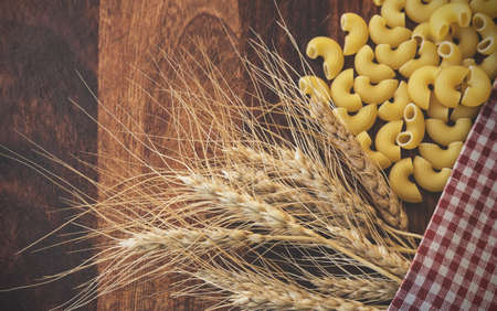 fascicle: Vintage toned picture of the ears of wheat with pasta on the wooden background. Stock Photo