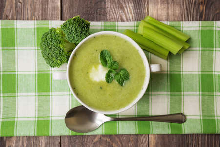 hot soup: Broccoli soup puree with mint and ricotta cheese on the dark wooden background. Top view. Stock Photo