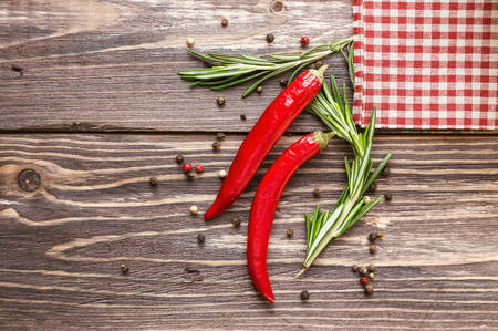 Red hot pepper and rosemary with checkered napkin on the rustic wooden background