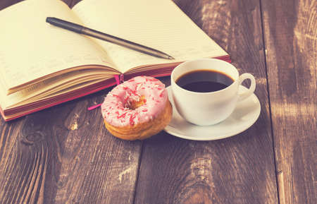 cup cakes: Black coffee, donut covered with pink icing and notepad on a rustic wooden background. Vintage toned pictire. Stock Photo