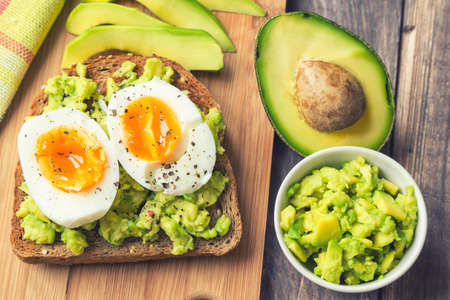 Toast with avocado and egg on rustic wooden background