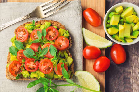 toast bread: Toast with avocado, tomatoes and basil on rustic wooden background